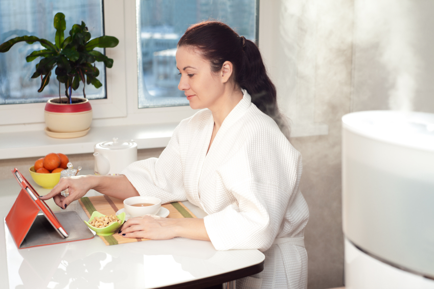 Woman drinking tea reading tablet near humidifier
